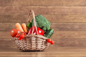 Wooden background with basket full of vegetables