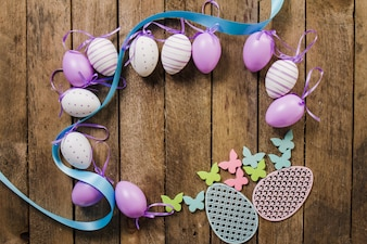 Wooden background with decorative easter eggs and butterflies