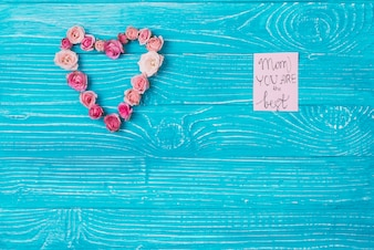 Wooden background with heart made of flowers and note for mother's day
