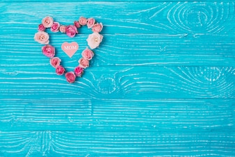Wooden background with heart made of pink flowers for mother's day