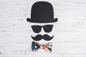 Wooden background with paper character and colored bow tie for father's day