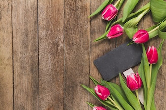 Wooden background with tulips and sign