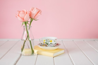 Wooden background with vase, coffee cup and book