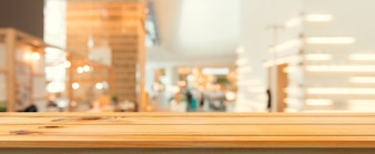 Wooden board empty table top blurred background. Perspective brown wood table over blur in coffee shop background. Panoramic banner - can be used mock up for montage products display or design.