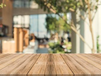 木製のボード空のテーブルの上にぼやけた背景。茶色の木製のテーブルは、コーヒーショップの背景にぼやけて見える - モンタージュ製品の表示やキービジュアルレイアウトのモックアップに使用できます。