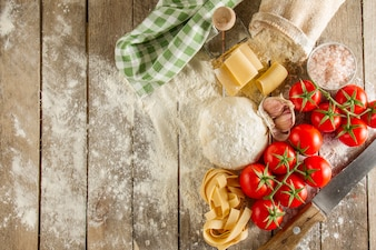 Wooden boards with flour and fresh ingredients