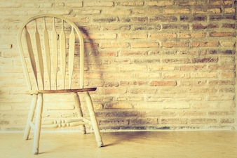 Wooden chair with a brick wall background