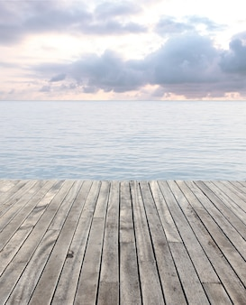 Wooden floor and blue sea with waves and cloudy sky