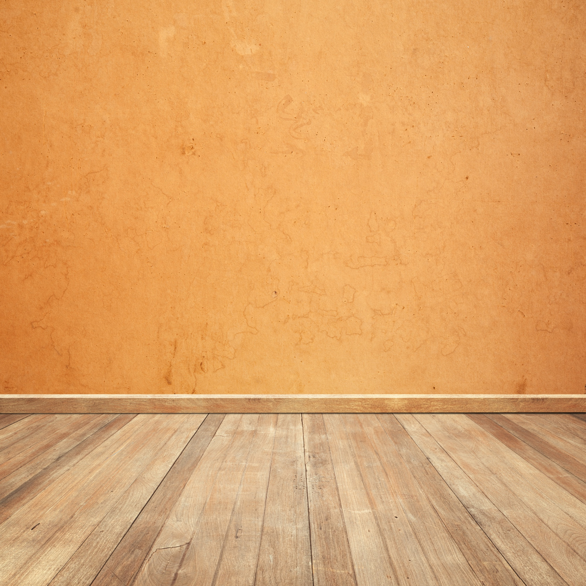Wooden floor with an orange wall background