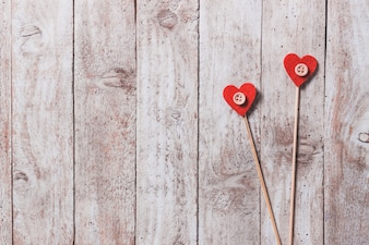 Wooden sticks with hearts in the end on a wooden table