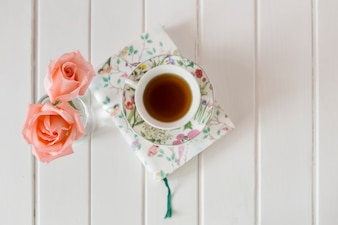 Wooden surface with book, flowers and cup of tea