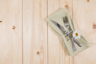 Wooden surface with cutlery and cute daisy