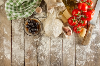 Wooden surface with flour and ingredients for cooking pasta
