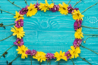 Wooden surface with flowers forming a frame
