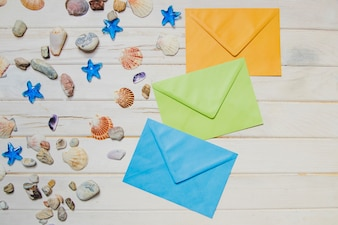 Wooden surface with seashells and colored envelopes