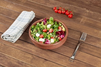 Wooden table with a tasty salad