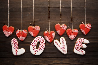 Word  love  made of cookies with heart-shaped cookies hanging from ropes on a wooden table