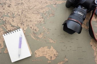 World map background with decorative camera and notebook
