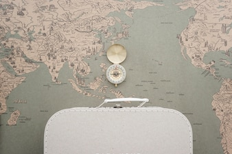 World map background with suitcase and compass