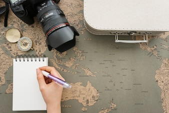 World map background with travel items and hand writing