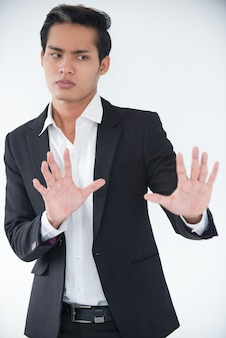 Worried businessman protecting himself with hands