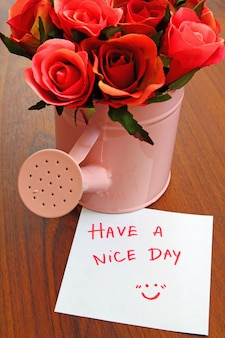 Writing message  have a nice day  with bouquet roses in watering can