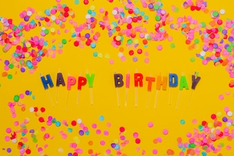 Yellow background with confetti and the letters  happy birthday