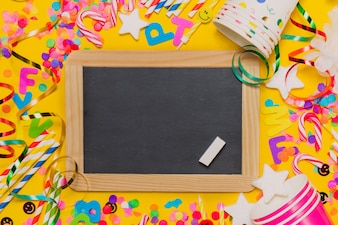 Yellow background with glasses, a chalkboard and party decoration