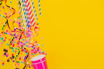 Yellow background with glasses and party decoration