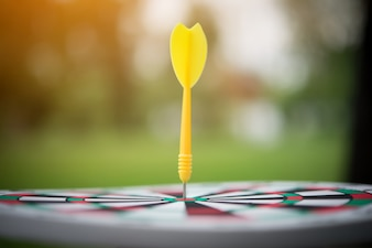 Yellow dart arrow hitting in the center of dartboard.