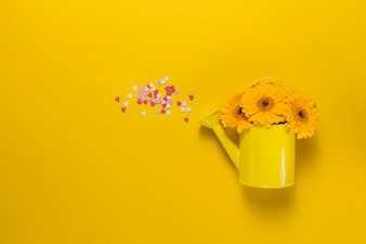 Yellow watering can with flowers and hearts confetti