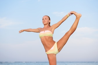 Yoga practice. Slim woman practicing by the sea