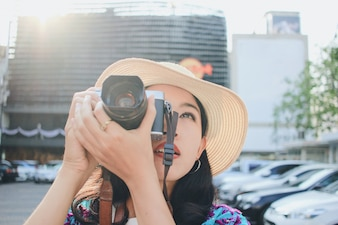 Young asian woman in casual clothes taking photos of the city and enjoying her vacation, travel concept