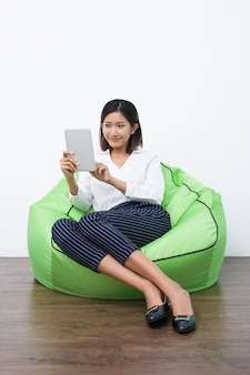 Young Asian woman sitting on beanbag using touchpad