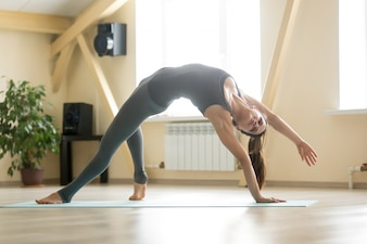 Young attractive woman standing in Camatkarasana pose, home inte