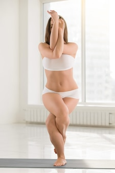 Young attractive woman standing in Garudasana pose, white color