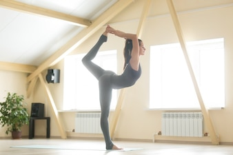 Young attractive woman standing in Natarajasana pose, home inter