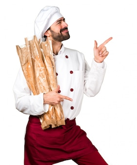 Young baker holding some bread and dancing