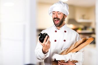 Молодой пекарь держит хлеб и держит старинные часы на кухне