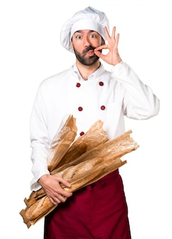Young baker holding some bread and making silence gesture