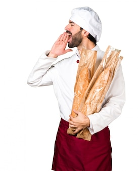 Young baker holding some bread and shouting