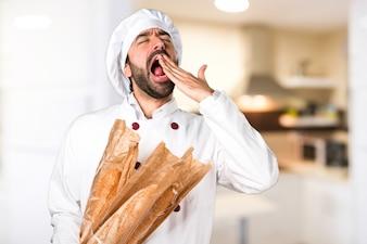 Молодой пекарь держит хлеб и зевает на кухне