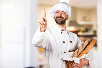 Young baker holding some bread touching on transparent screen in the kitchen