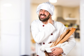 Young baker holding some bread with neck pain in the kitchen