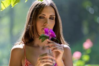 Young beautiful girl smells flowers, against green summer garden.