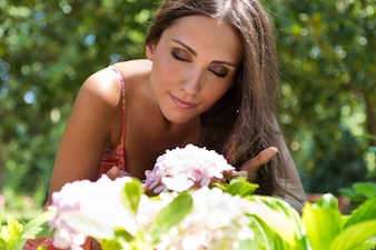 Young beautiful girl smells flowers, against green summer garden.