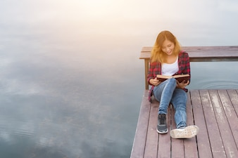 Young beautiful hipster woman relaxing sitting on pier reading b