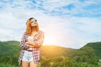Young beautiful hipster woman standing crossed arms amidst natur