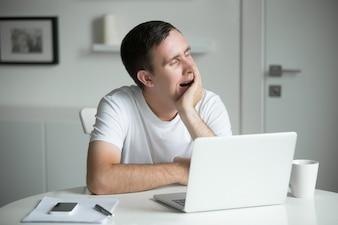 Молодой скучный, зевая, сидя на белом столе возле ноутбука