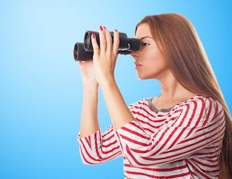 Young brunette girl in striped shirt spying through binoculars